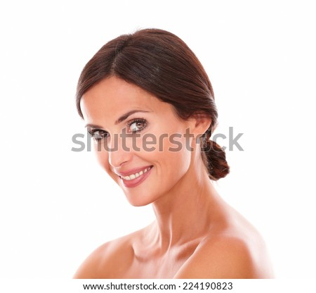 Head and shoulders portrait of sexy young female with natural smile while smiling at camera with nude shoulders on isolated studio - stock photo