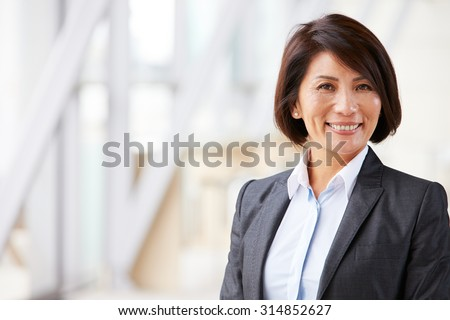 Head and shoulders portrait of smiling Asian businesswoman - stock photo