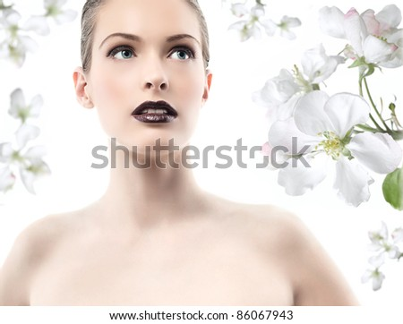 head and shoulders portrait of young attractive caucasian woman  with spring flowers - stock photo