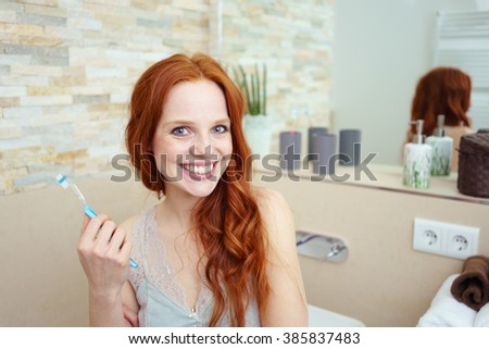 Head and Shoulders Portrait of Young Woman with Long Red Hair Standing in Bathroom with Toothy Smile and Holding Toothbrush - Brushing Teeth as part of Morning Hygiene Routine - stock photo