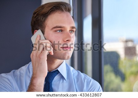 Head and shoulders shot of a handsome young businessman wearing a corporate tie, looking thoughtfully and optimistically through a window in his office while using his mobile phone - stock photo