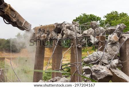 Head hammer backhoe to repair the destroyed demolition concrete bridge collapse. - stock photo