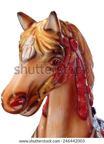 Head of a horse in a red bridle on a merry-go-round or carousel in a fairground or amusement park for children on an isolated background - stock photo