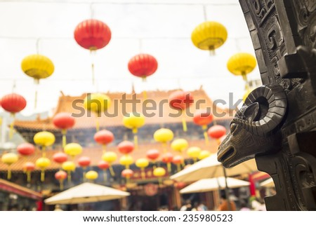 head of aries ornamenting door of Wong Tai Sin temple (north Kowloon, Hong Kong), with hanging Chinese paper lanterns, incense smoke and the temple itself in background (selective focus on ornament) - stock photo