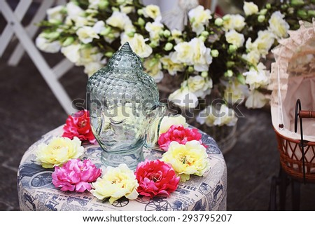 head of Buddha surrounded by flowers - stock photo