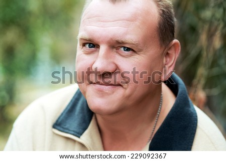Head of friendly, handsome middle-aged man looking sidewards into camera. - stock photo