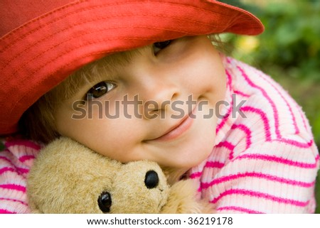 Head of girlie embracing her teddy-bear with peaceful expression - stock photo