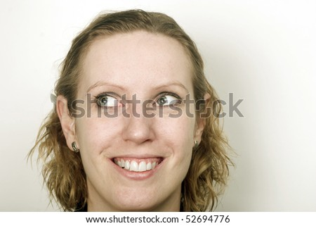 Head of young blond woman with eyes turned into left upper corner. Lot of space around. - stock photo