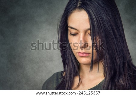 Head portrait of a pretty young brunette girl in serene expression - stock photo