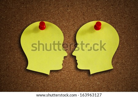 Head shape paper note reminder with thumb tack pin on cork board concept for face off, health care, dementia, memory, discussion and business meeting - stock photo