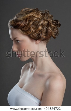 Head shot in profile on a neutral, seamless background of a beautiful young woman with light brown or blonde hair and grey eyes who is wearing plain white strapless top. - stock photo