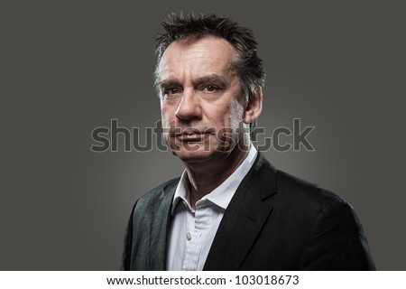 Head Shot Portrait of Handsome Middle Age Business Man in Suit Grey Background High Contrast Grunge Look - stock photo