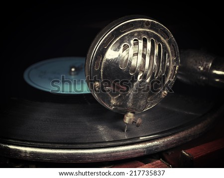 Head with an old gramophone needle on the vinyl disc closeup - stock photo
