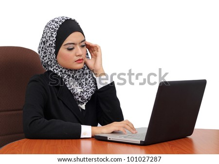 Headache and Stress at work. Young professional muslim woman stressed and tired with headache sitting at office desk - stock photo