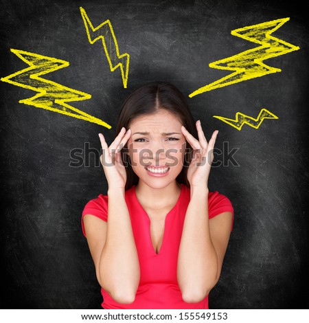 Headache - migraine and stress concept with woman in pain massaging temples for headache cure. Multi-ethnic Caucasian / Asian woman on blackboard background. - stock photo