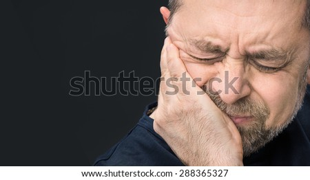 Headache. Portrait of an elderly man with face closed by hand on dark background with copy-space - stock photo