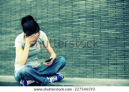 headache young asian woman sit and use her cellphone  - stock photo