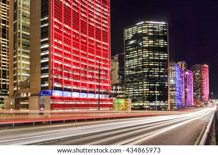 Headlamps of passing cars on a motorway in Sydney, Australia, during annual vivid Sydney light show. Illuminated high-rise buildings standing behind elevated highway. - stock photo
