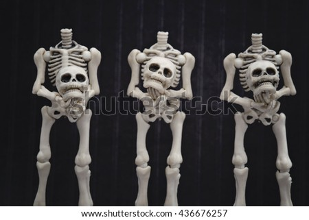 Headless skeletons holding their own head - stock photo