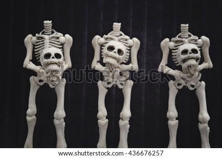 Headless skeletons holding their own head - stock photo