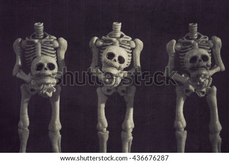 Headless skeletons holding their own heads grungy textured - stock photo