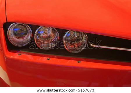 headlight  closeup of a red Italian sportcar - stock photo