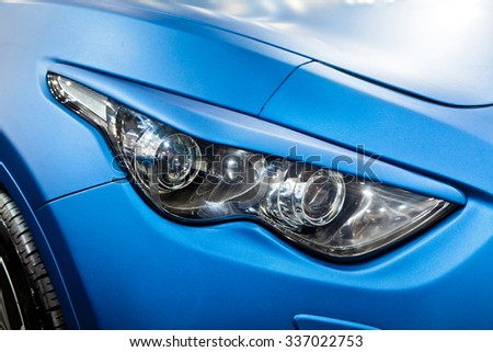 Headlight of blue car close up - stock photo