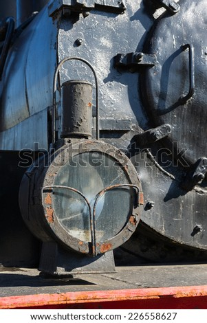 Headlight of the ancient steam locomotive. Petroleum lamp and a metal reflector inside the metal cage. Black boiler in the background. Vertical, portrait orientation photography - stock photo