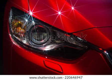 Headlights and hood of sport red car with silver stars - stock photo