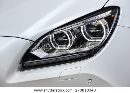 Headlights and hood of sport white car with led lamps - stock photo