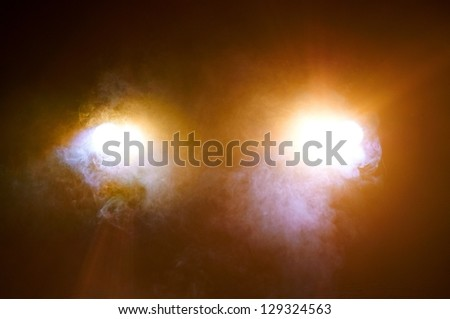 Headlights of a car in smoke - stock photo