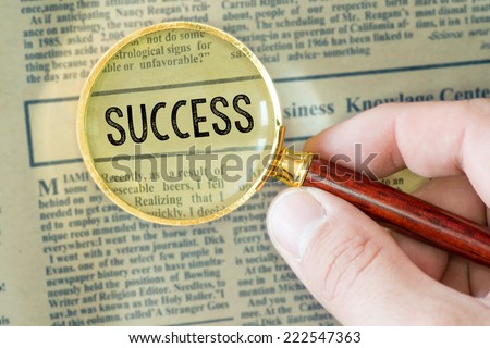 Headline of newspaper through magnifying glass, with Success word - stock photo