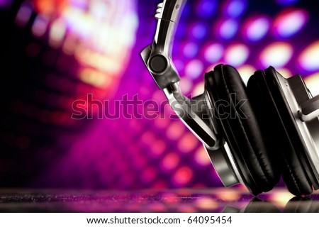 headphones against purple disco background - stock photo