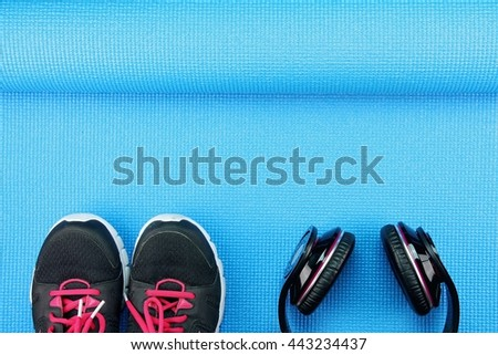 Headphones and sport shoes on yoga mat background, Fitness and exercise equipment, Entertainment workout concept. - stock photo