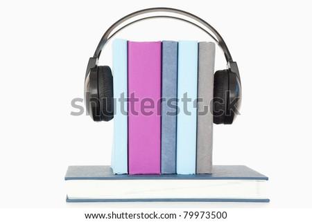 Headphones around books against a white background - stock photo