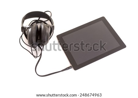 Headphones connected to a last generation tablet computer - stock photo