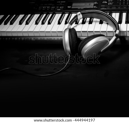 Headphones on musical synthesizer keyboard. Headphones on electronic piano - stock photo