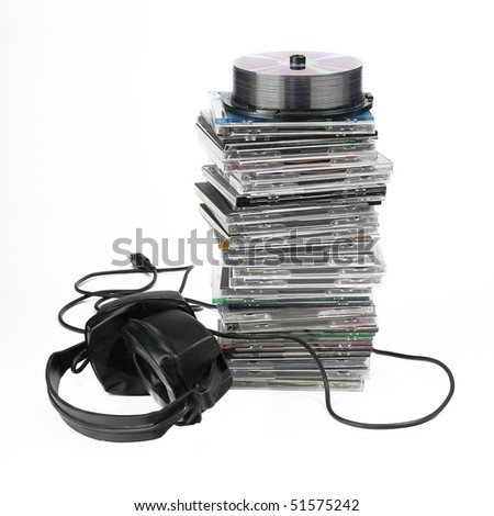 headphones on stack of CDs on white background - stock photo