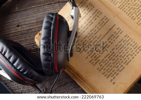 Headphones on the old book. Concept of listening to audiobooks. - stock photo