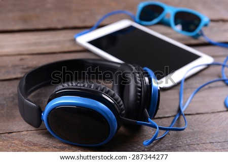 Headphones with tablet on wooden background - stock photo