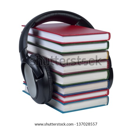 Headphones worn on a stack of books with color covers isolated on white background. - stock photo