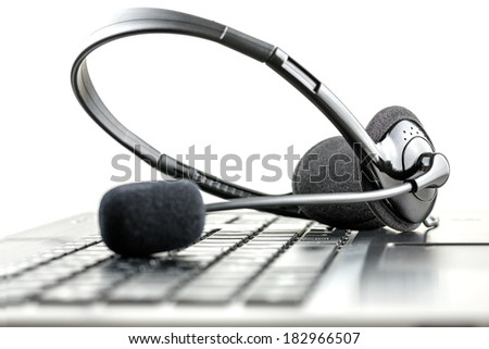 Headset lying on a laptop computer keyboard conceptual of telemarketing, call center, client services or online support. - stock photo