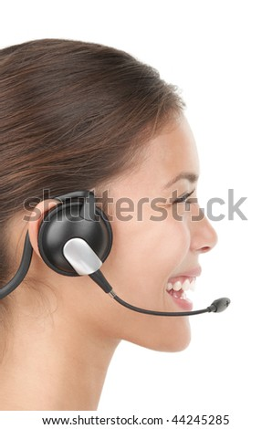 Headset woman in profile - smiling very kindly. Closeup of beautiful young mixed race chinese / caucasian secretary / assistant speaking with headphones in call center. Isolated on white background. - stock photo