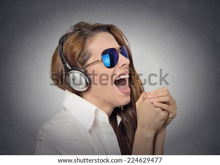 Headshot beautiful happy woman with sunglasses singing with microphone listening to music grey background. Positive human face expression emotion feeling. Happiness, holiday club disco leisure concept - stock photo