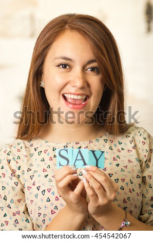 Headshot charming brunette woman holding up small letters spelling the word say and smiling to camera - stock photo