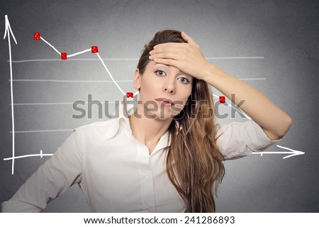 Headshot depressed business woman looking stressed financial market chart graphic going down on grey office wall background. Poor economy mistake crisis meltdown loss concept. Face expression emotion - stock photo