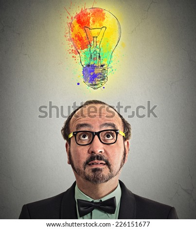 headshot man having brilliant idea colorful lightbulb above head isolated grey wall background. Human face expression emotion perception. Creativity imagination dynamism intelligence iq concept - stock photo