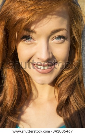 Headshot of a beautiful young woman with ginger hair, blue eyes and white teeth. - stock photo