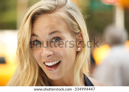 Headshot of a wide eyed woman with a big smile and surprised look. - stock photo