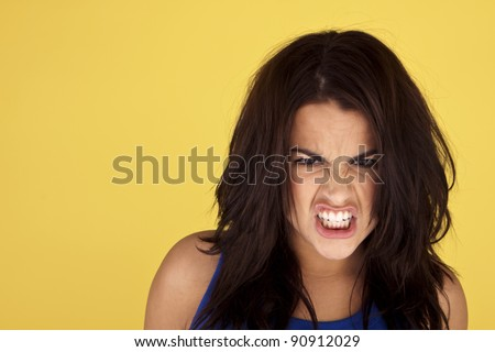 Headshot of a young and angry woman on a yellow background. Angry woman. - stock photo